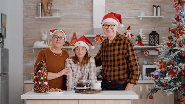 Portret van een gelukkige familie met een kerstmuts die naar de camera kijkt die aan tafel staat in een met kerst versierde k...