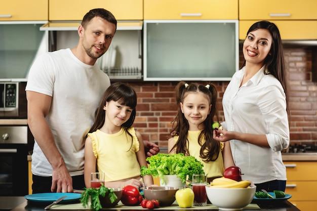 Portret van een gelukkige familie, moeder vader en twee dochters, koken salades in keuken thuis. gezond eten concept