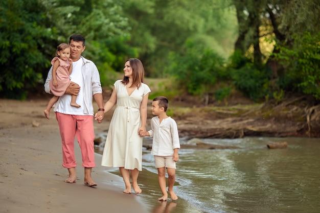 Portret van een gelukkige familie. moeder vader zoon en dochter op vakantie voor een wandeling op de zanderige oever van een prachtige rivier.