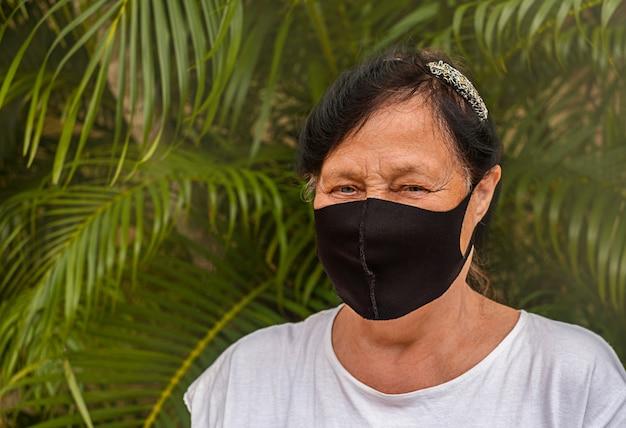 Portret van een gelukkige gepensioneerde die een veiligheidsmasker draagt.