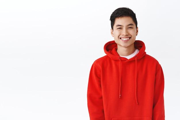 Portret van een gelukkige, glimlachende aziatische hipster man, jonge kerel in rode hoodie die vrolijk glimlacht, camera enthousiast kijkt, positieve stemming uitdrukt, blij of tevreden is, witte muur.