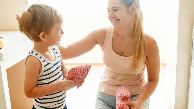Portret van een gelukkige glimlachende jonge vrouw met een 3 jaar oude peuterkindzoon die in de keuken tegen een groot raam staat