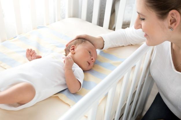 Portret van een gelukkige glimlachende moeder die haar baby streelt die in bed ligt
