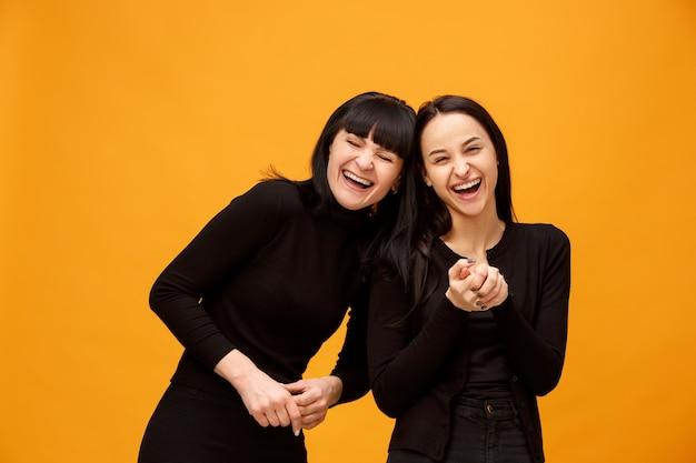 Portret van een gelukkige glimlachende moeder en dochter op geel