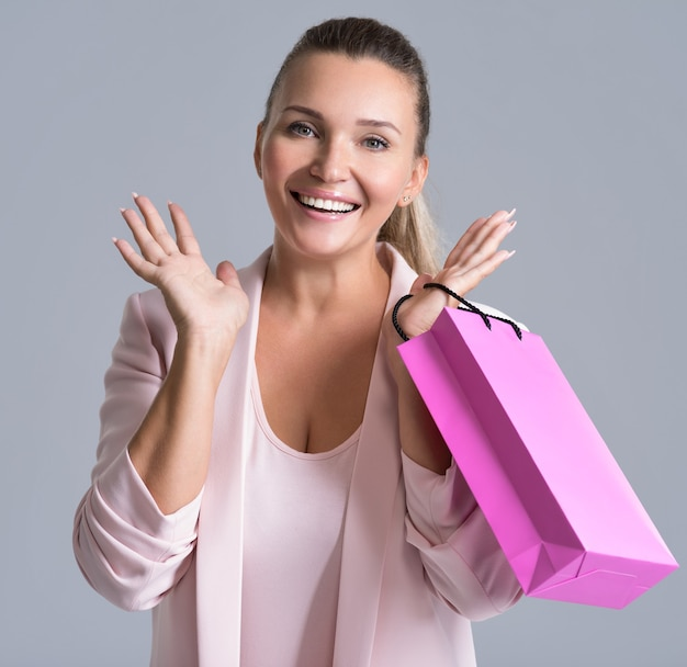 Portret van een gelukkige glimlachende verrassingsvrouw met roze boodschappentas.
