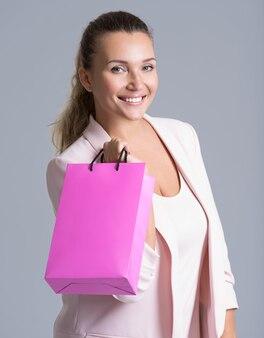 Portret van een gelukkige glimlachende vrouw met roze boodschappentas.