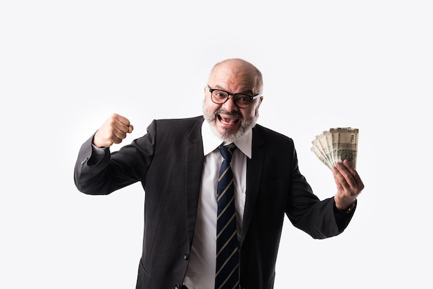 Portret van een gelukkige indiase aziatische senior zakenman met indiase bankbiljetten van vijfhonderd coupures holding