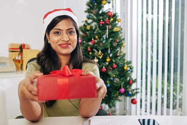 Portret van een gelukkige indiase zakenvrouw die een kerstcadeau geeft terwijl ze aan de kantoortafel zit