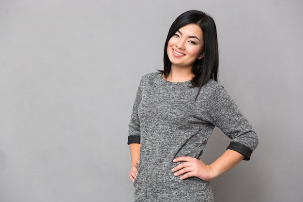 Portret van een gelukkige japanse vrouw die voorzijde over grijze muur bekijkt