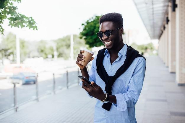 Portret van een gelukkige jonge afrikaanse man die aan de telefoon chat en op straat loopt met een kopje koffie.