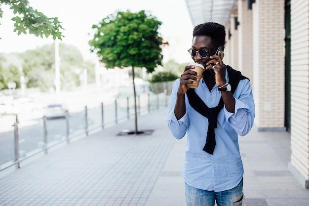 Portret van een gelukkige jonge afrikaanse man die aan de telefoon praat en op straat loopt met een kopje koffie.