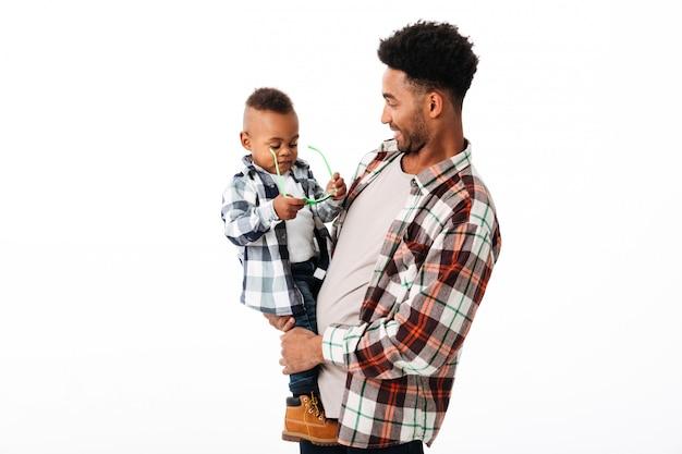 Portret van een gelukkige jonge afrikaanse man die zijn zoontje houdt