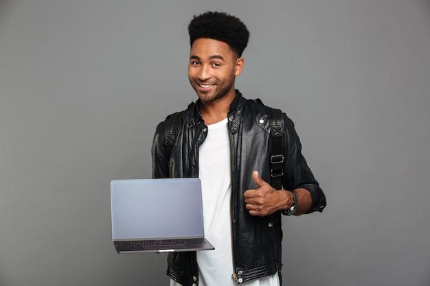 Portret van een gelukkige jonge afrikaanse man in lederen jas