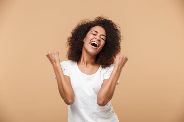 Portret van een gelukkige jonge afrikaanse vrouw vieren