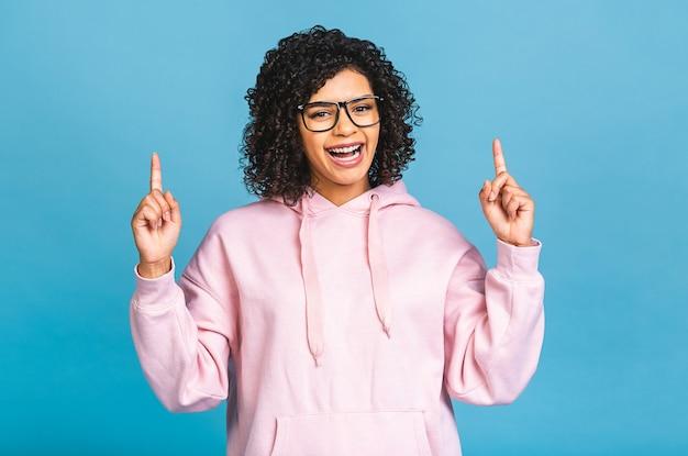Portret van een gelukkige jonge afro-amerikaanse zwarte vrouw wijzende vingers weg op kopie ruimte geïsoleerd op blauwe achtergrond.
