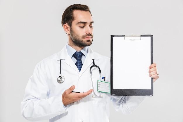 Portret van een gelukkige jonge arts die naar het klembord kijkt terwijl hij een gezondheidskaart vasthoudt die over een witte muur is geïsoleerd