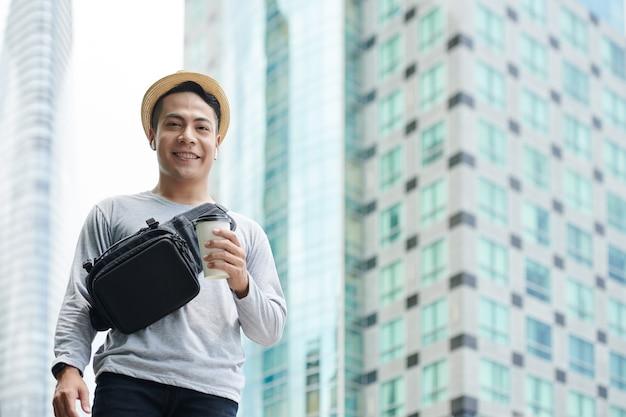 Portret van een gelukkige jonge aziatische man in een strohoed met een afhaalkoffiekop die tegen hoge gebouwen in de grote stad staat