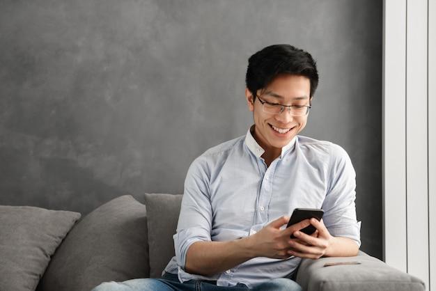 Portret van een gelukkige jonge aziatische man met behulp van mobiele telefoon