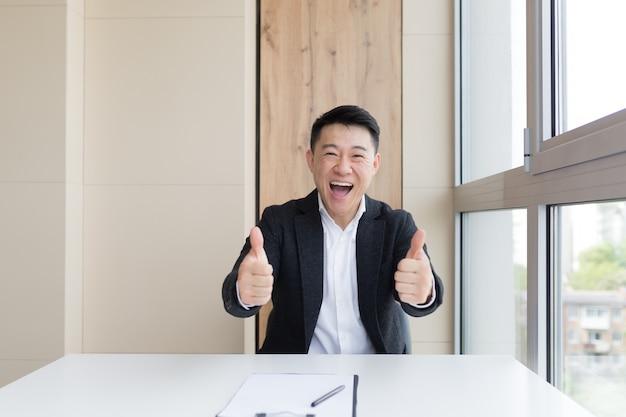 Portret van een gelukkige jonge aziatische mannelijke kantoormedewerker die naar de camera kijkt en binnenshuis glimlacht. close up van een vriendelijke manager in een formeel pak en wit overhemd zittend op het werk. zakenman gevoel ontvangen