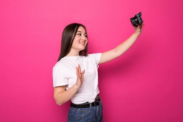 Portret van een gelukkige jonge aziatische vrouw gekleed in witte jurk en zomer hoed met fotocamera en weg kijken naar kopie ruimte over roze muur