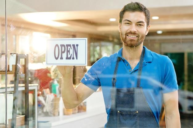Portret van een gelukkige jonge barista in een spijkerschort die een open bord op de glazen wand van zijn café of winkel steekt