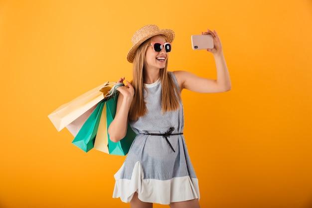 Portret van een gelukkige jonge blonde vrouw in de zomerhoed