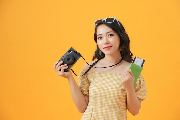 Portret van een gelukkige jonge camera van de vrouwenholding en het tonen van paspoort terwijl status geïsoleerd over geel