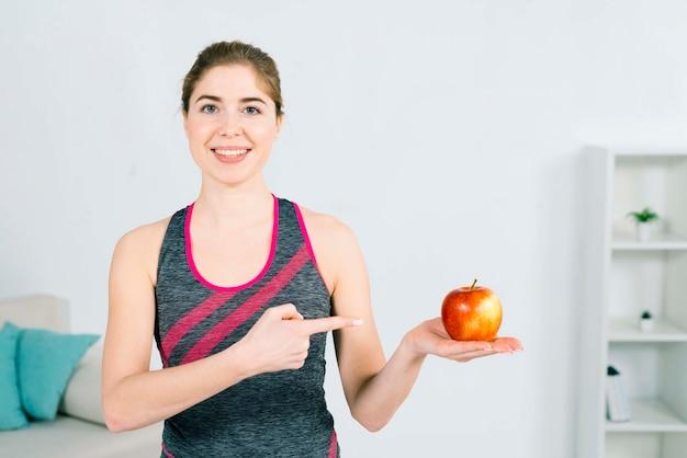 Portret van een gelukkige jonge fitness vrouw met rode appel in de hand