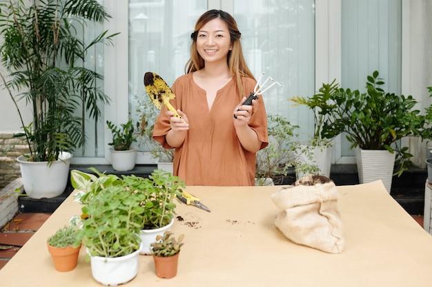 Portret van een gelukkige jonge glimlachende vrouw die aan een grote tafel staat met een troffel en een tuinvork in handen, klaar om bloemen te melden