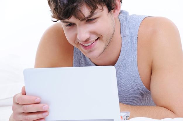 Portret van een gelukkige jonge kerel met laptop