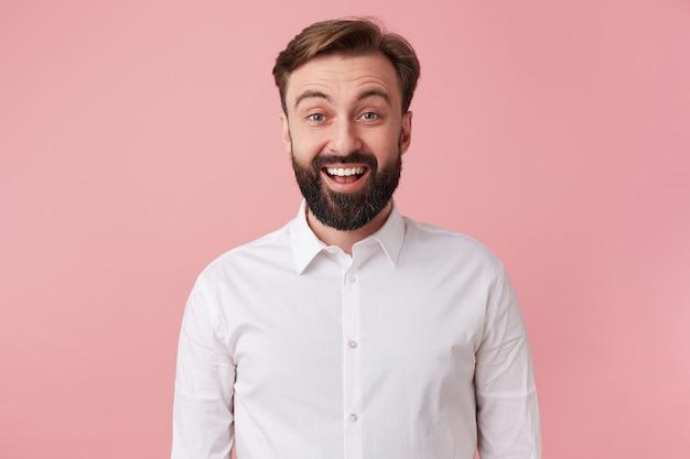 Portret van een gelukkige jonge knappe bebaarde man, gekleed in een wit overhemd, hoorde het goede nieuws. kijkend naar de camera en lachend geïsoleerd op roze achtergrond.