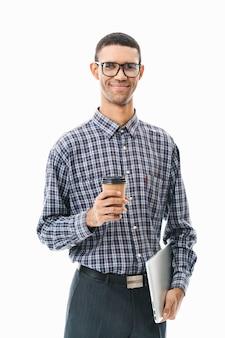 Portret van een gelukkige jonge man die geruite overhemd draagt dat zich over wit bevindt, koffiekop en laptop computer houdt
