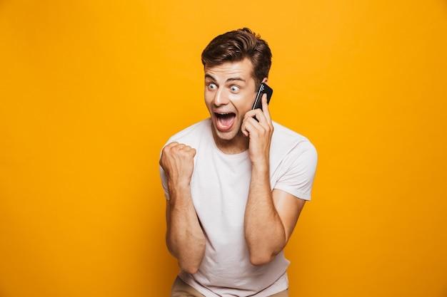 Portret van een gelukkige jonge man die op mobiele telefoon spreekt