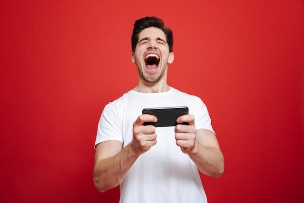 Portret van een gelukkige jonge man in wit t-shirt vieren