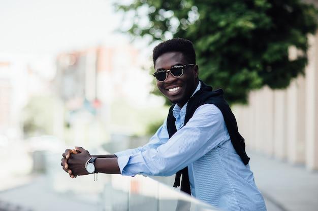 Portret van een gelukkige jonge man, toerist die loopt en lacht in de straat van de stad.