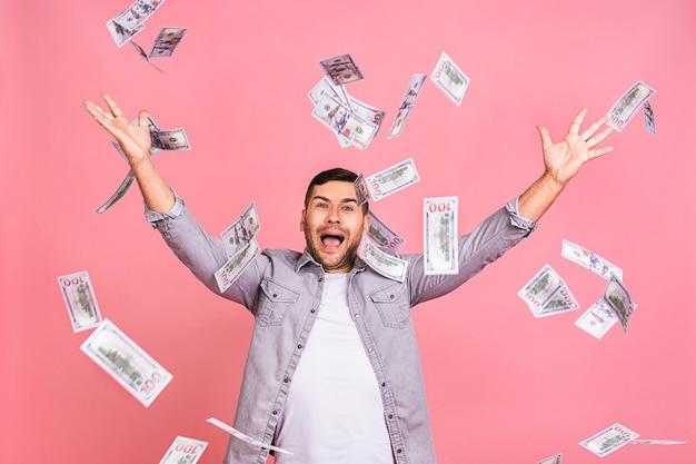Portret van een gelukkige jonge mens die geldbankbiljetten weggooit