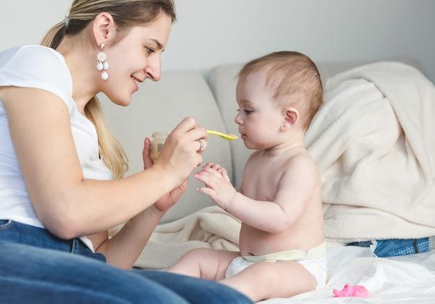 Portret van een gelukkige jonge moeder die haar baby op bed voedt met een lepel