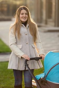 Portret van een gelukkige jonge moeder die met een kinderwagen op straat loopt