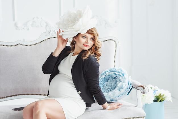 Portret van een gelukkige jonge mooie zwangere vrouw met een witte grote bloem in haar zat op de witte bank
