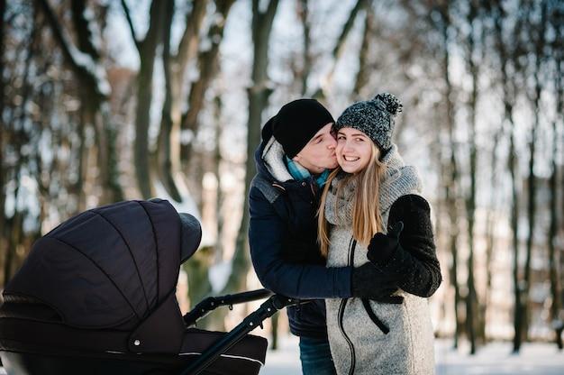Portret van een gelukkige jonge ouders staan en kussen met een wandelwagenbaby in een winterpark