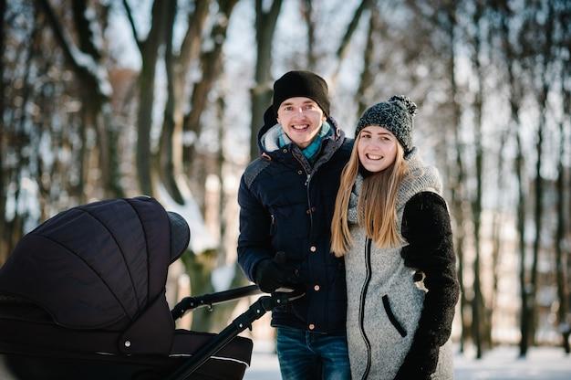 Portret van een gelukkige jonge ouders staan met een wandelwagen en een baby in een winterpark. familie concept.