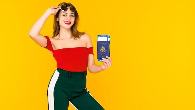 Portret van een gelukkige jonge reiskaartjes en paspoort van de vrouwenholding over geel. focus op paspoort.