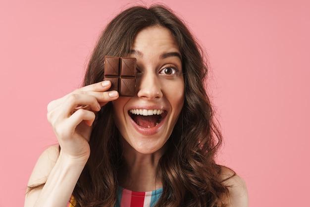 Portret van een gelukkige jonge schattige vrouw die zich voordeed over een roze muur met chocoladesnoepjes