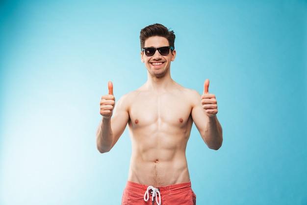 Portret van een gelukkige jonge shirtless man in zwemshort
