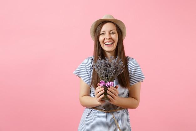 Portret van een gelukkige jonge tedere vrouw in blauwe jurk, hoed met boeket van mooie paarse lavendel bloemen geïsoleerd op heldere trending roze achtergrond. internationale vrouwendag vakantie concept.