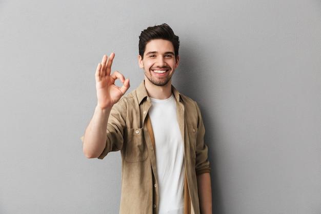 Portret van een gelukkige jonge toevallige mens die ok gebaar toont