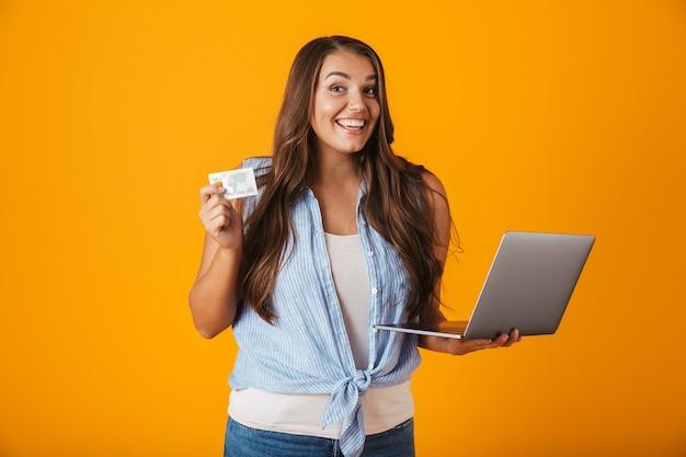Portret van een gelukkige jonge toevallige vrouw, die laptop computer houdt, die plastic creditcard toont