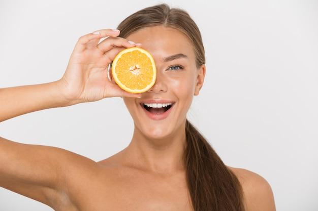 Portret van een gelukkige jonge topless geïsoleerde vrouw, met gesneden sinaasappel op haar gezicht