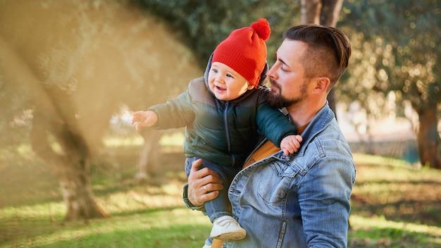 Portret van een gelukkige jonge vader die met zijn kleine zoon loopt