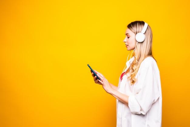 Portret van een gelukkige jonge vrouw die aan muziek met hoofdtelefoons en mobiele telefoon luistert die over gele muur wordt geïsoleerd